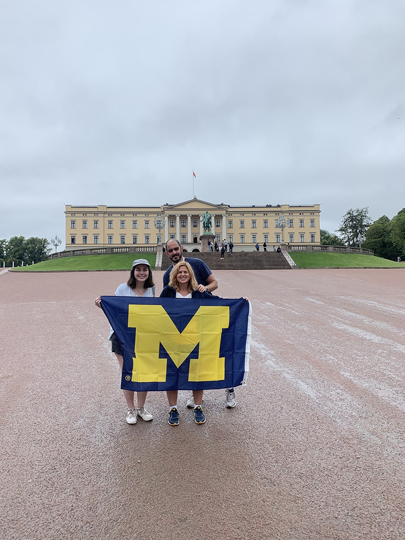 Meredith Weingarden, '91, her husband, Adam, and their daughter, Emilie, showed off their U-M flag in front of the Royal Palace in Oslo, Norway, in August. Missing from the picture is her son, Noah, who is a current U-M student.
