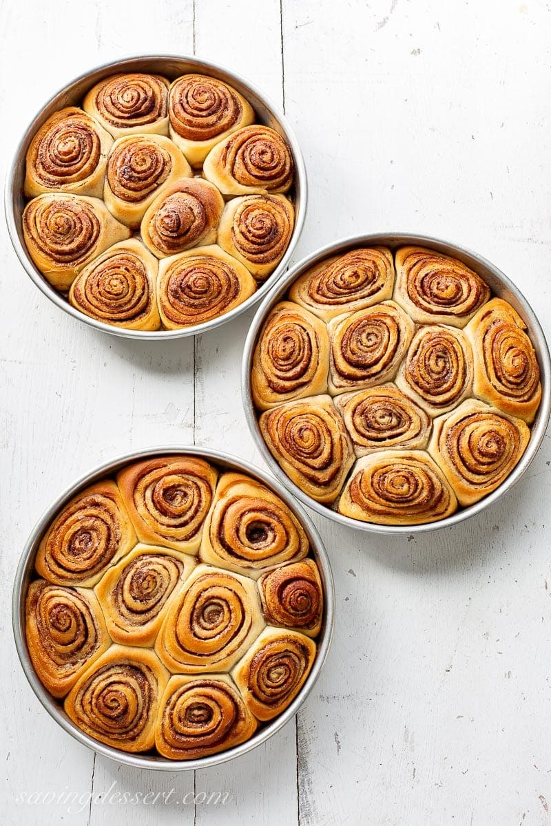 Three pans of fresh from the oven cinnamon rolls.
