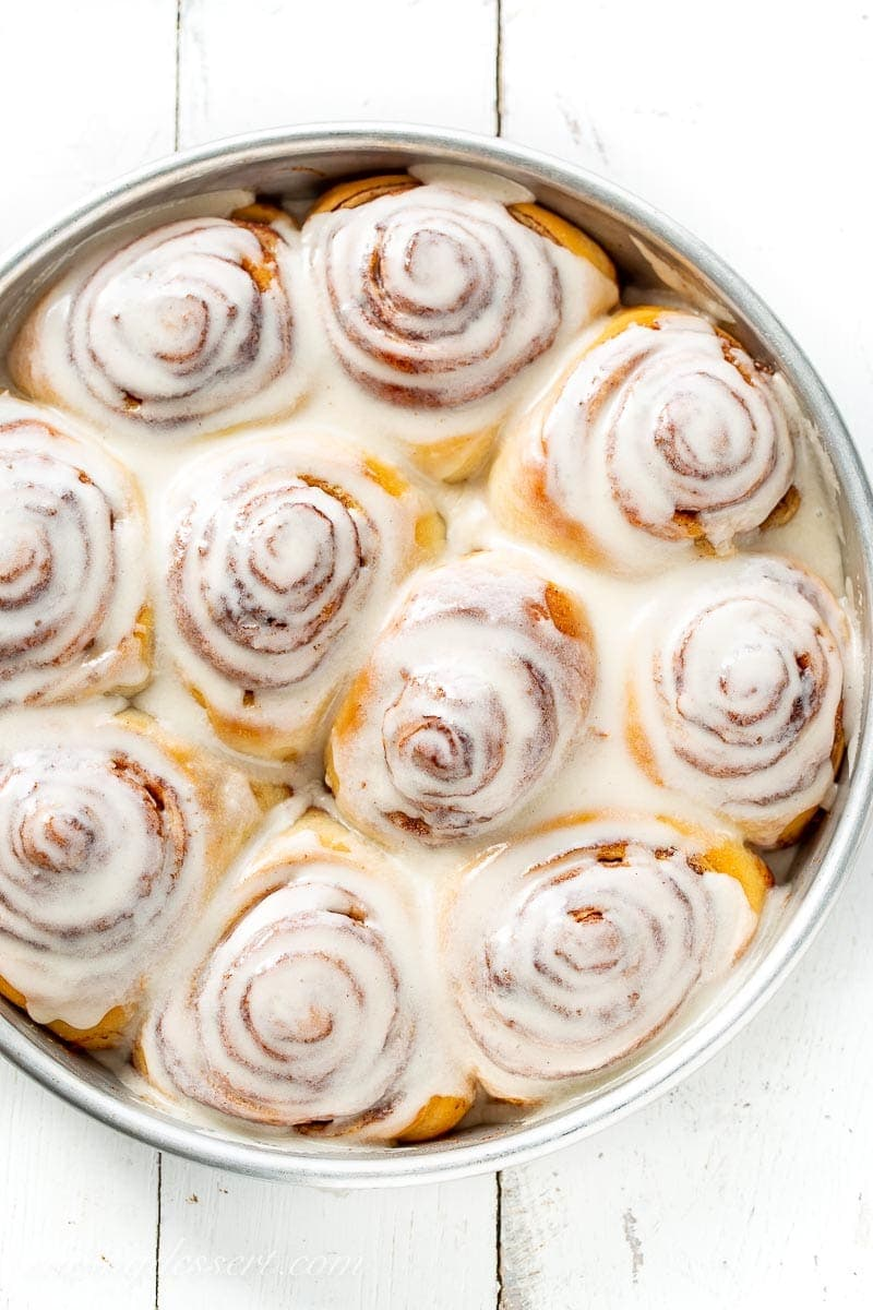A close up a a pan of frosted cinnamon rolls