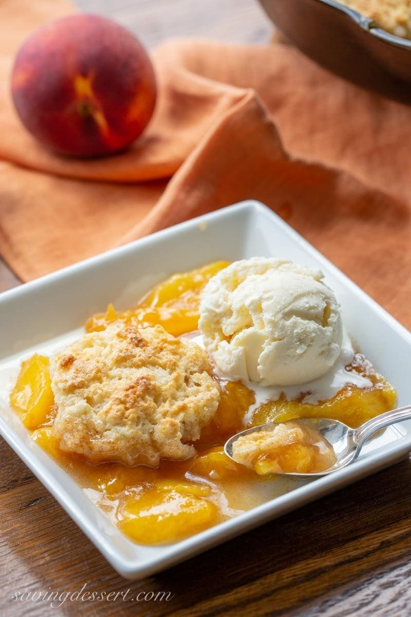 A bowl with old fashioned peach cobbler with a shortcake biscuit crust and a scoop of vanilla ice cream