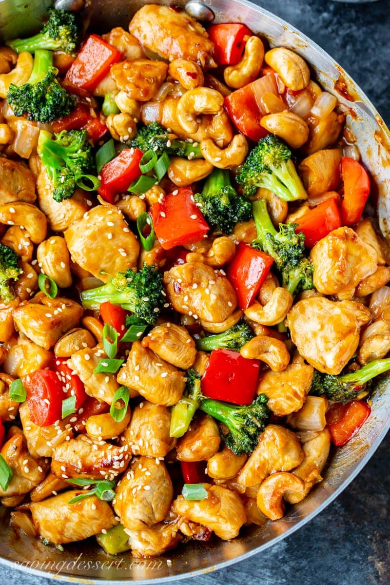 A skillet filled with red peppers, broccoli and cashew chicken