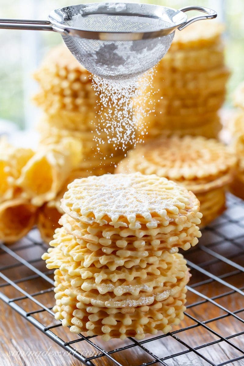 A stack of anise flavored pizzelle cookies dusted with powdered sugar