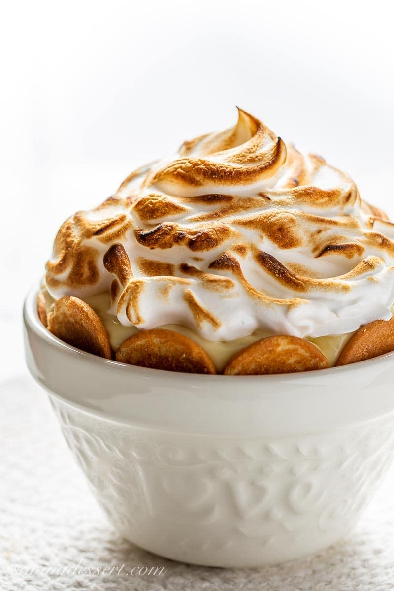 A side view of a white bowl filled with pudding and vanilla wafers topped with a toasted meringue
