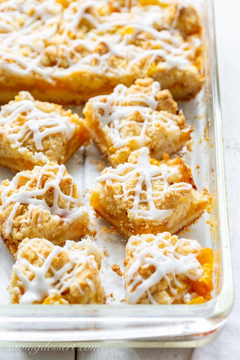 A baking pan filled with fresh peach crumb bars topped with a drizzled icing