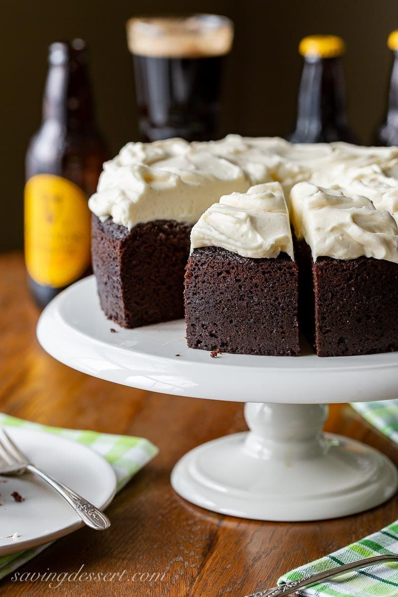 A sliced dark chocolate Guinness cake topped with cream cheese icing