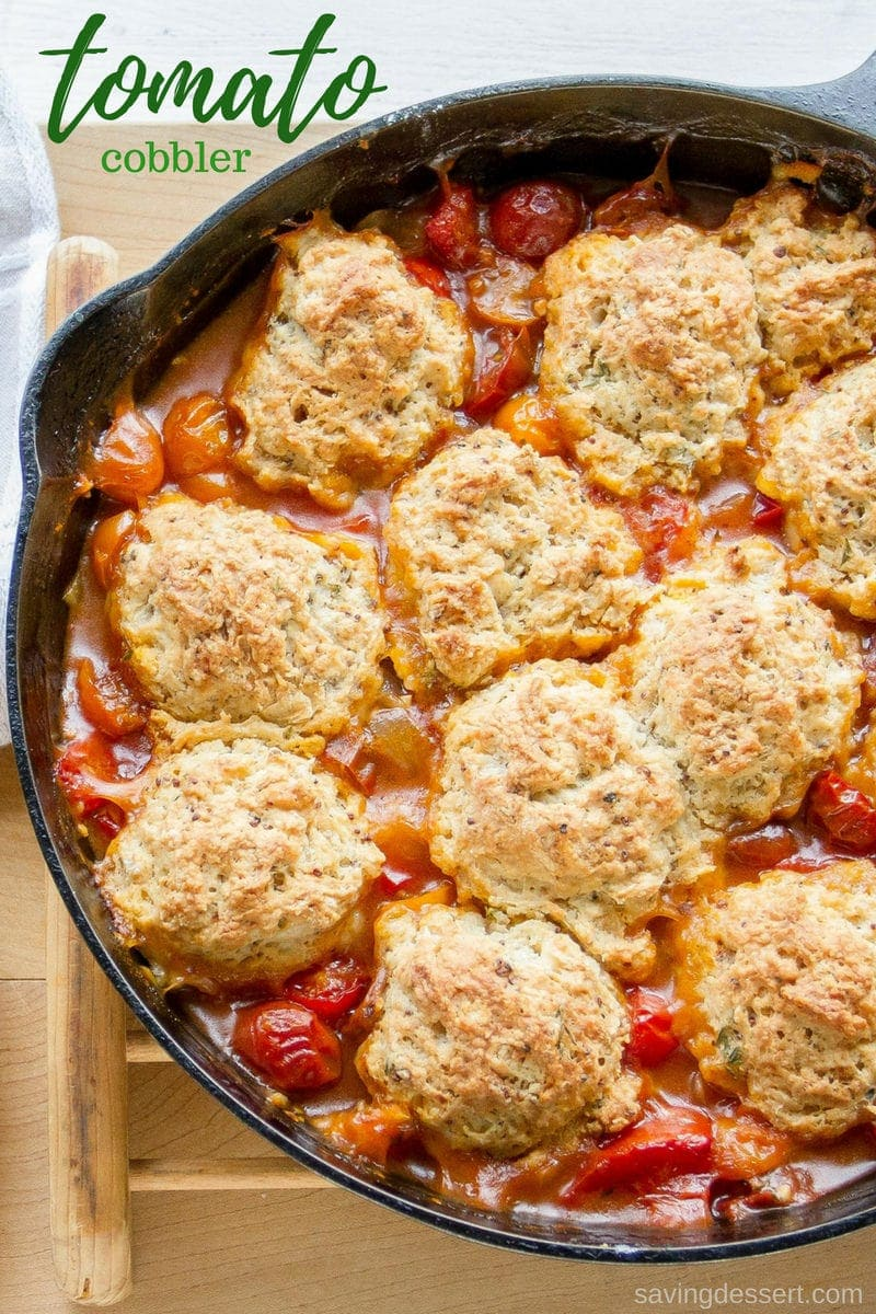 A cast iron skillet filled with savory tomato cobbler with herbed biscuit topping