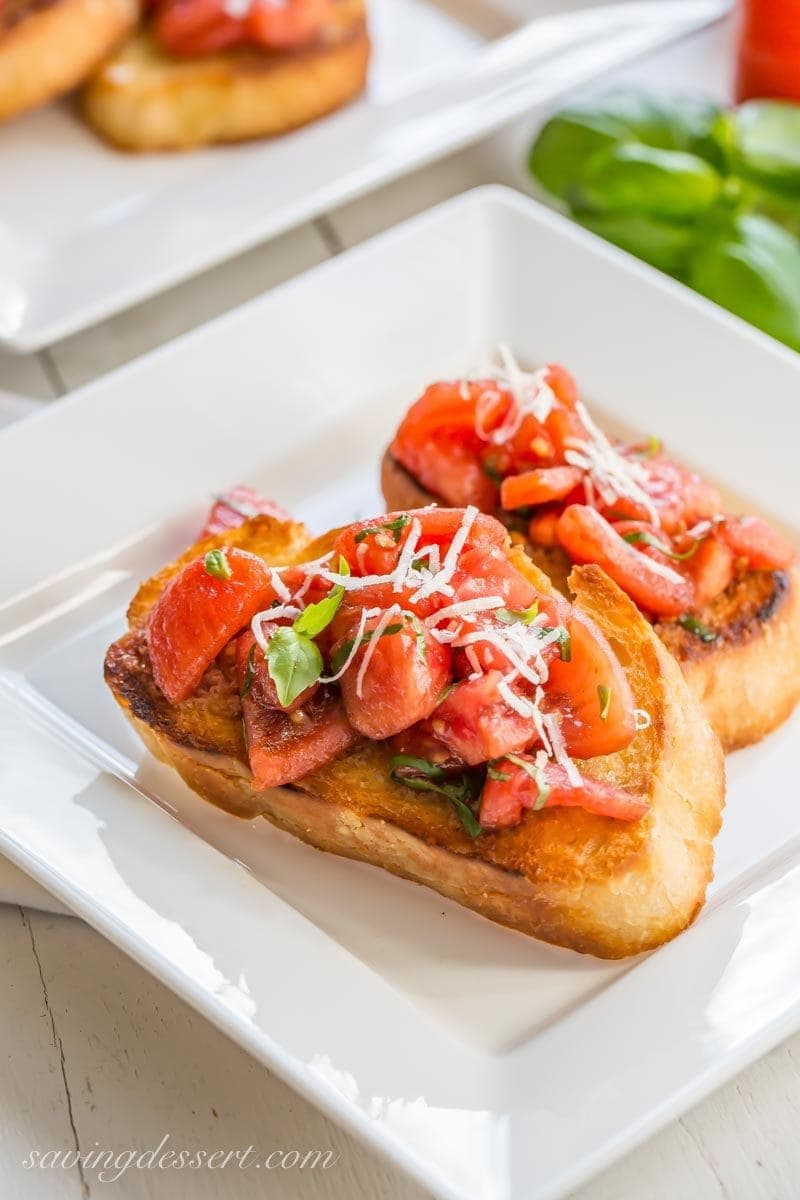 A plate of fresh tomato Bruschetta topped with basil and Parmesan cheese