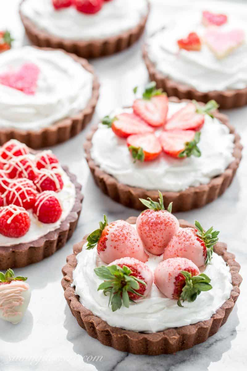 Chocolate Tarts with White Chocolate Mousse filling topped with sprinkle hearts, strawberries and raspberries