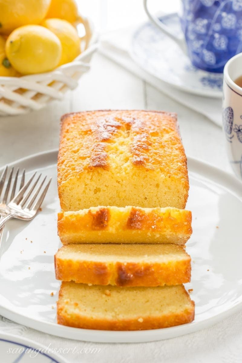 A sliced lemon ricotta pound cake with a cup of tea
