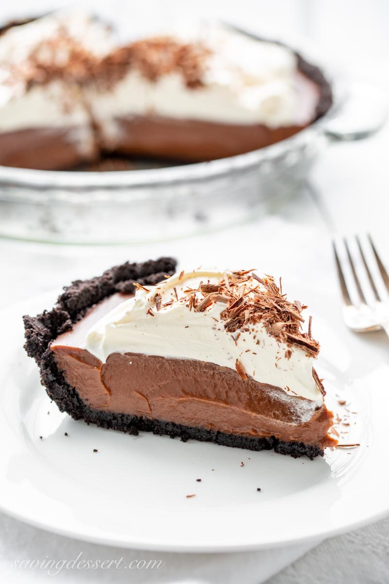 A slice of chocolate cream pie with whipped cream, chocolate shavings and a chocolate crust.