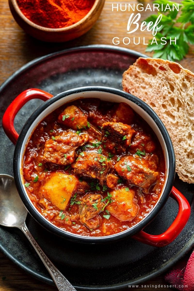 A bowl of Hungary style beef Goulash served with bread and garnished with fresh parsley