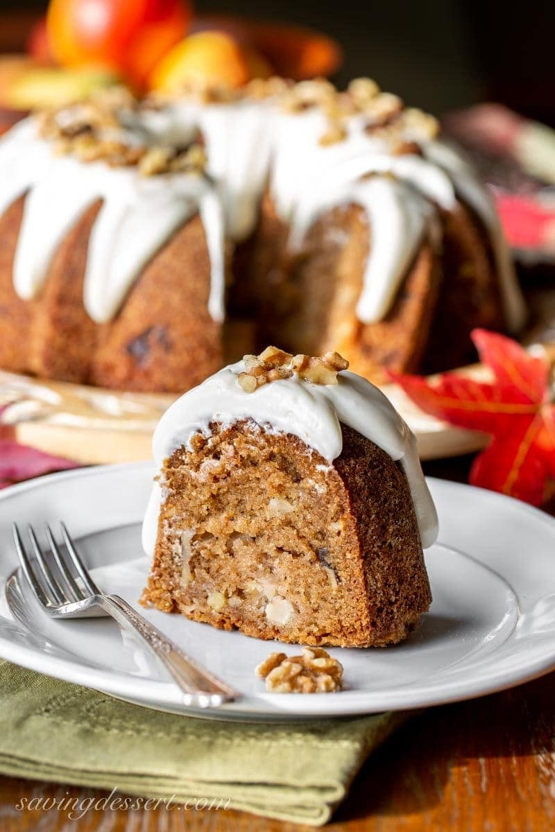 A slice of fresh apple bundt cake with cream cheese icing and walnuts