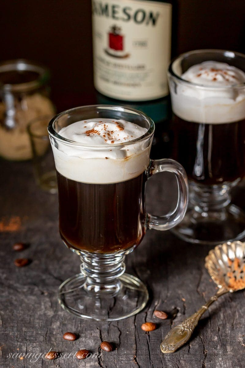 Mugs of hot Irish Coffee with lightly whipped cream on top