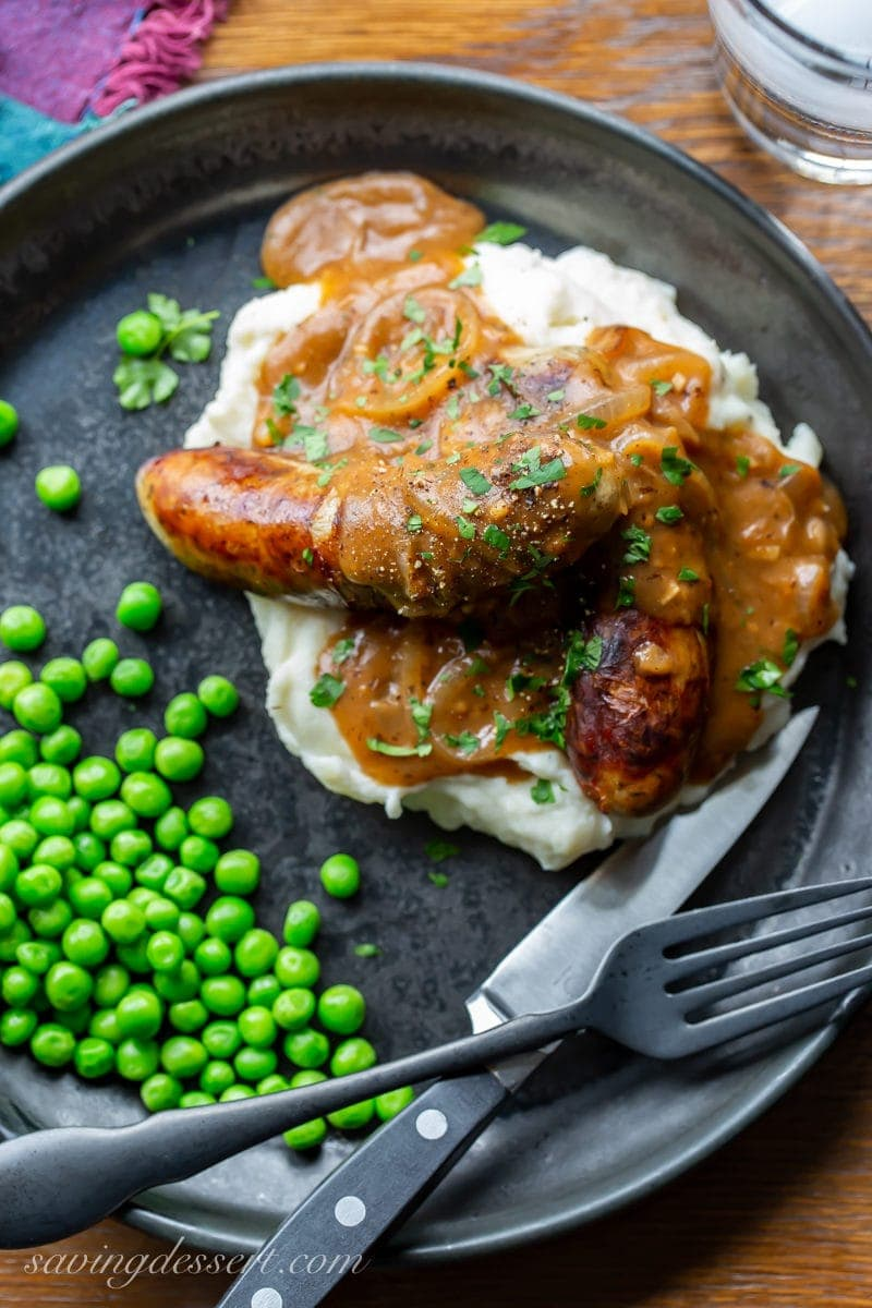 A plate of bangers and mash with peas and onion gravy