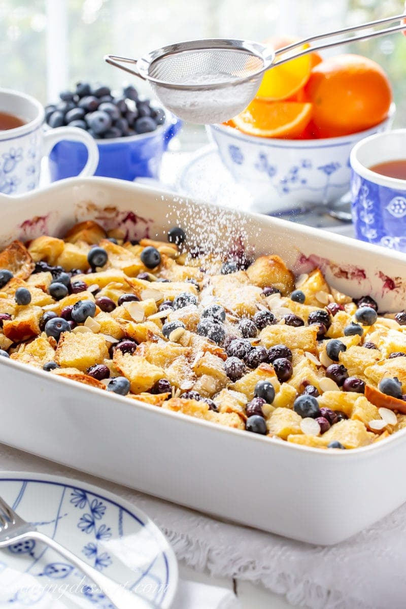 A baking dish with an overnight blueberry french toast casserole being dusted with powdered sugar.