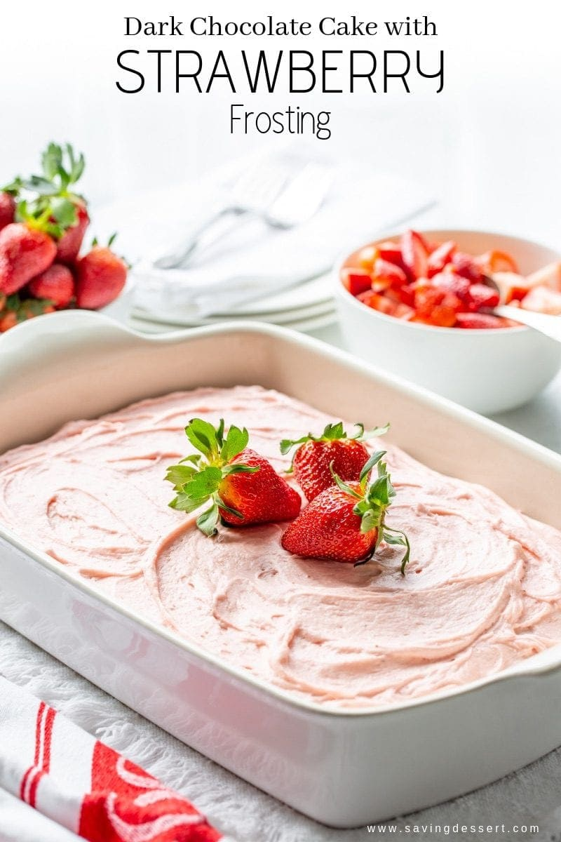 A dark chocolate sheet cake with fresh strawberry frosting garnished with fresh strawberries.