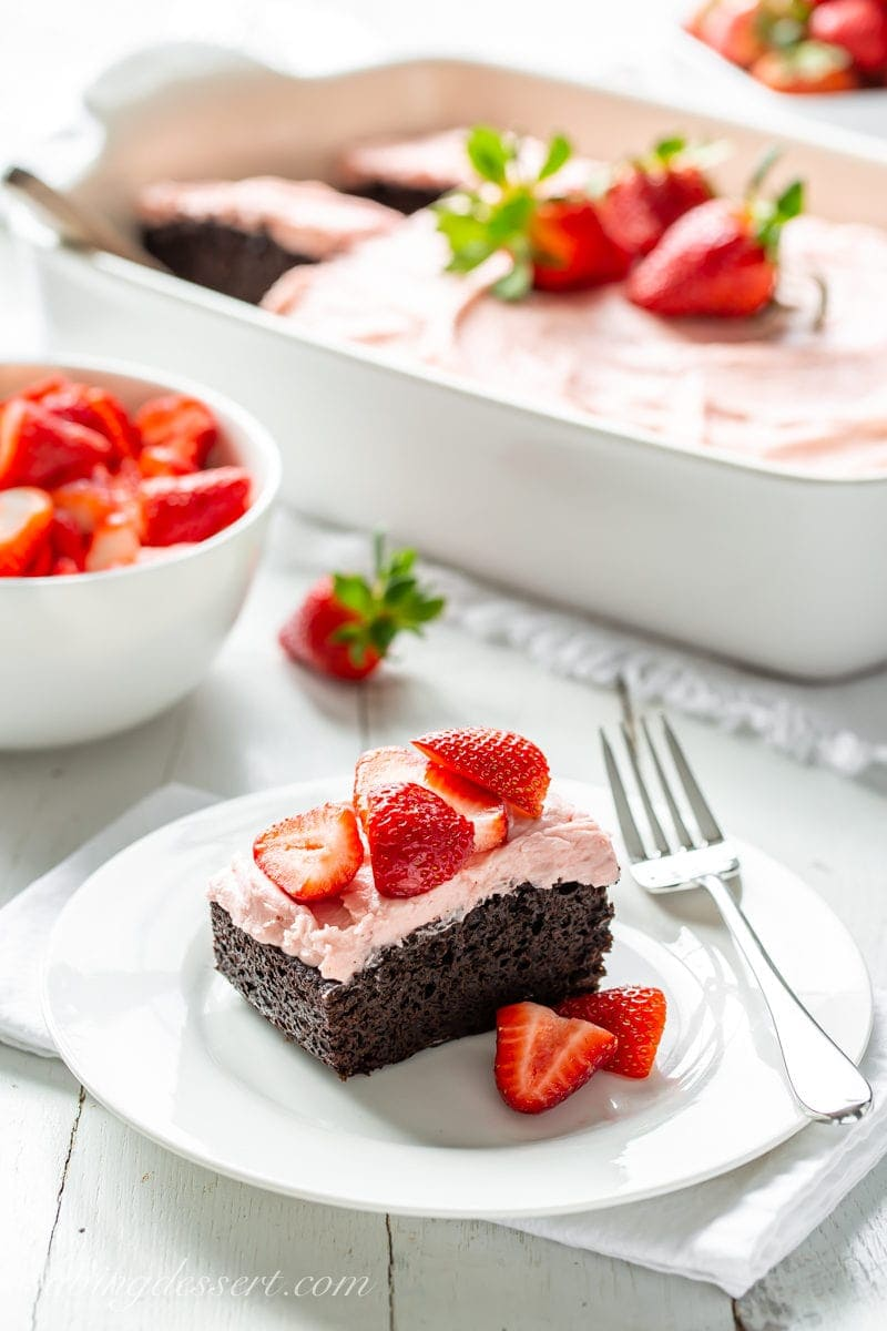 A slice of dark chocolate sheet cake topped with strawberry frosting and served with fresh strawberries