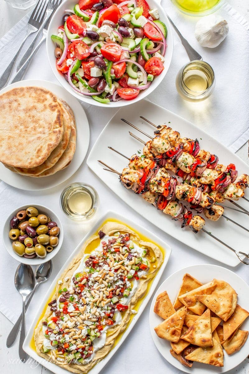 A Greek dinner party with Grilled Greek Chicken Kabobs, a bowl of Greek Salad, Greek Layered Hummus Dip, Whole Wheat Pita breads, wine and olives