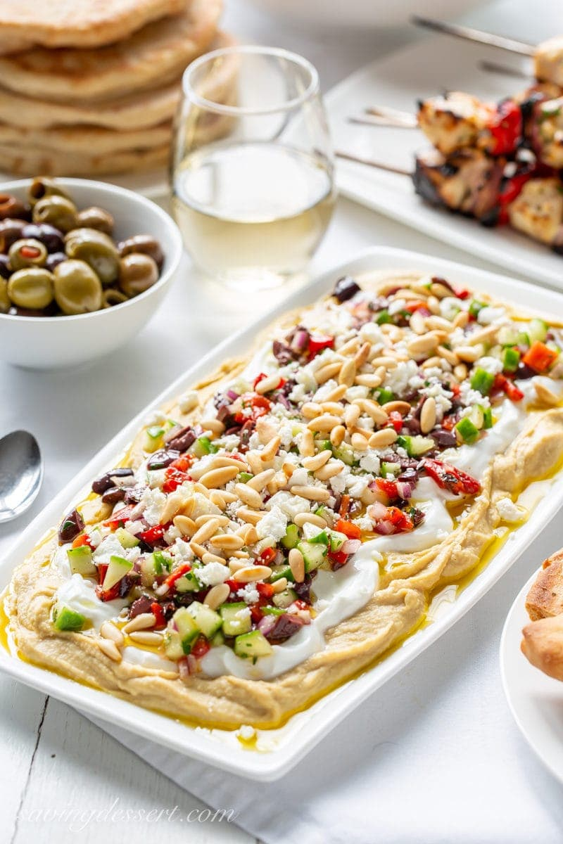 A platter of Greek Layered Hummus Dip with yogurt, olives, red peppers, pine nuts and cucumbers