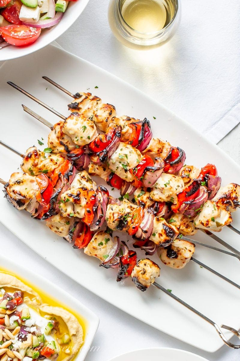 A plate of grilled Greek Chicken skewers with red peppers and purple onions served with hummus and Greek salad