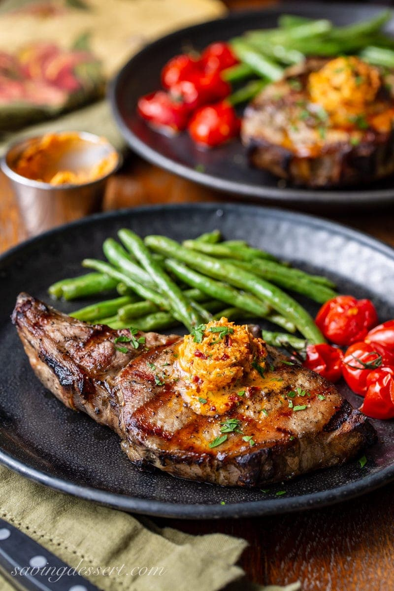 A plate with a grilled pork chop topped with chipotle butter and served with green beans and roasted tomatoes