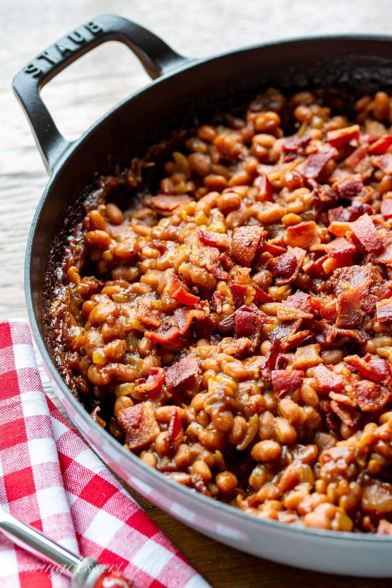 A casserole dish full of oven baked beans topped with chopped bacon