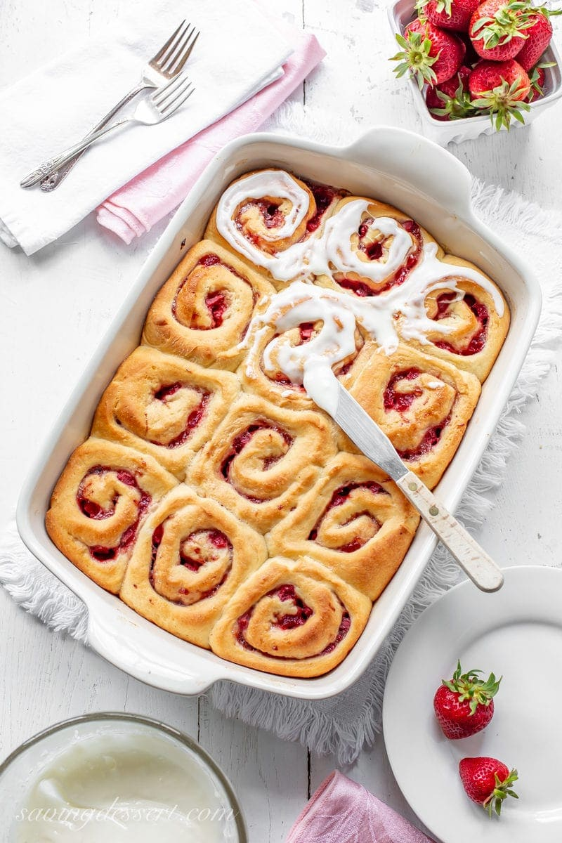 A pan of strawberry sweet rolls topped with cream cheese frosting