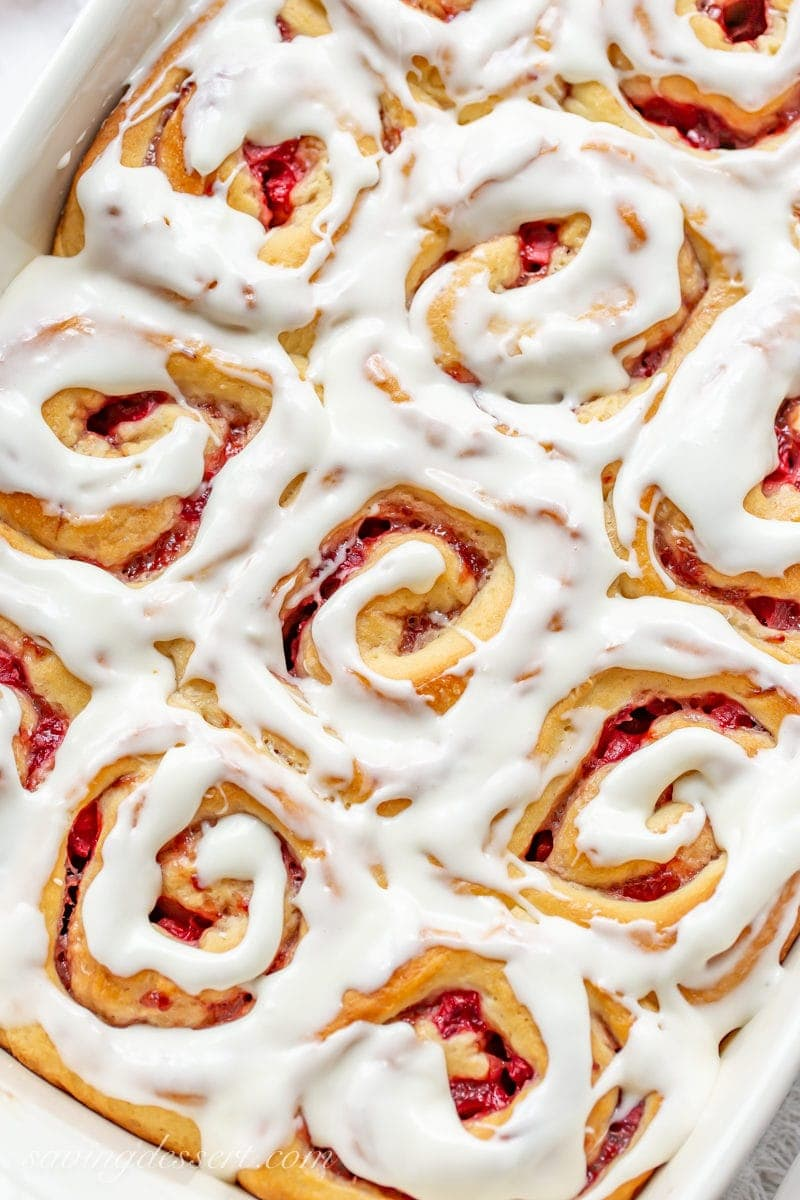 A close up of a pan of Strawberry Sweet Rolls with cream cheese icing