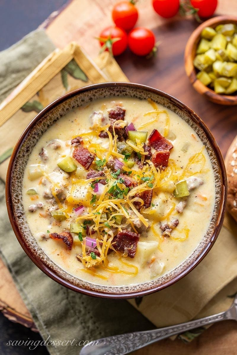 A bowl of cheeseburger soup garnished with bacon, pickles, onions and extra cheese