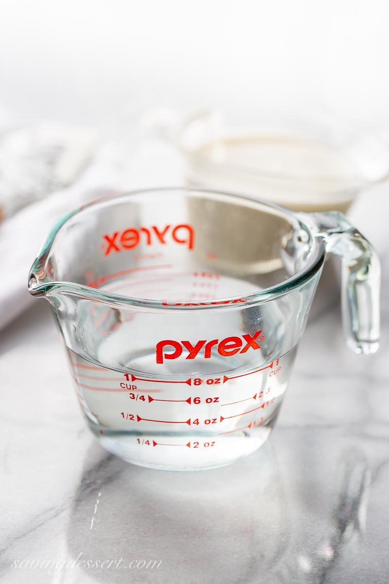 A glass measuring cup with a spout, filled with water