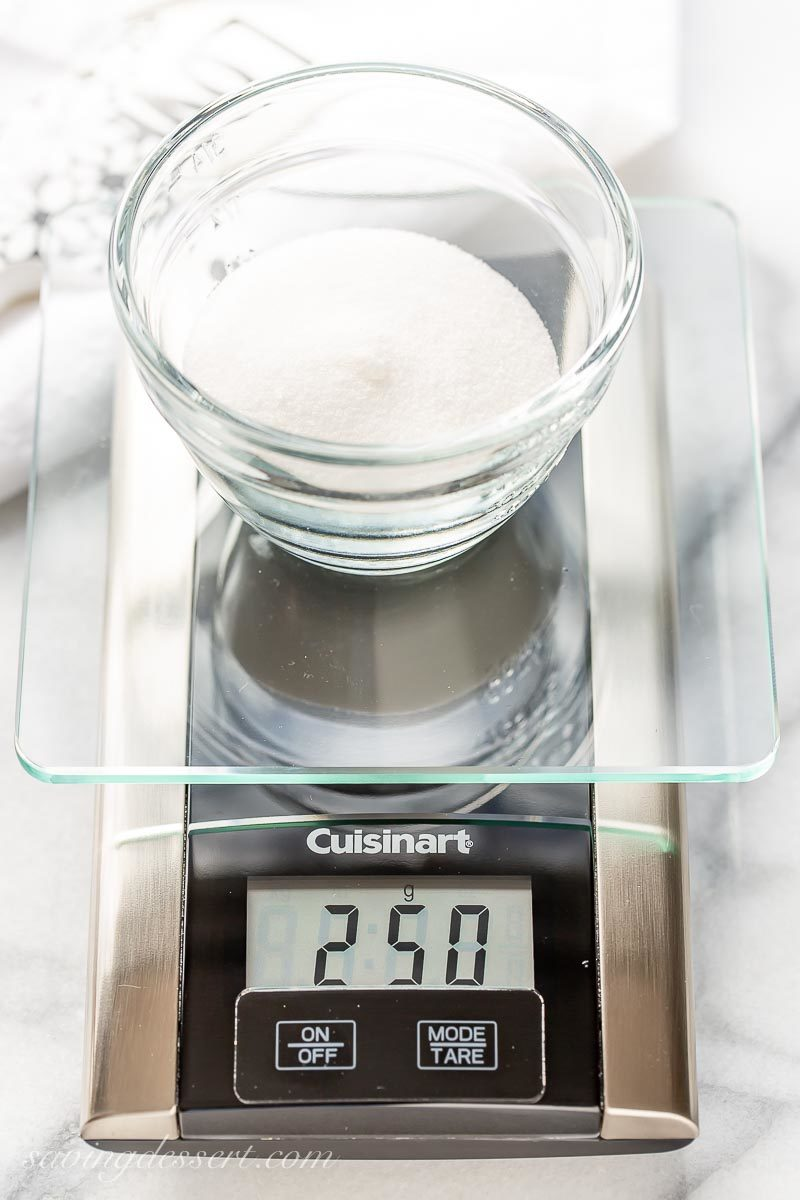 A digital kitchen scale weighing granulated sugar in a bowl for another one of our favorite baking tips