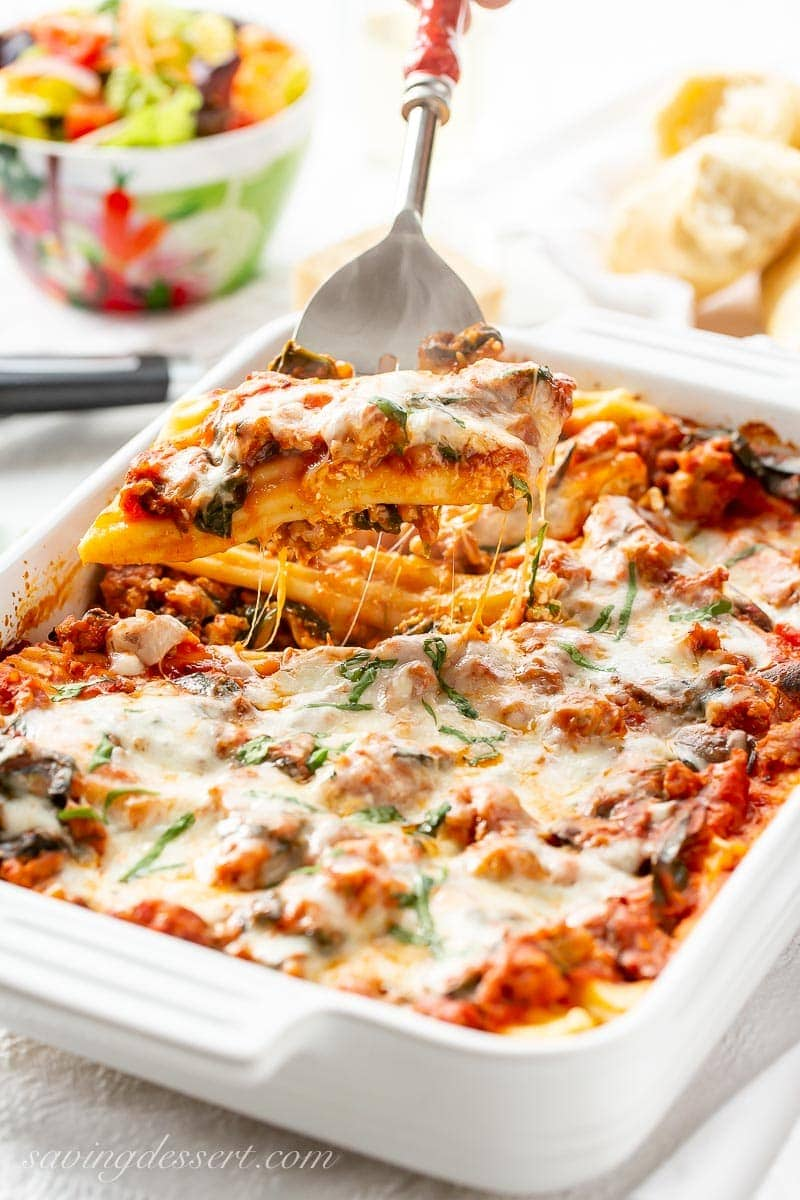 A spoonful of stuffed manicotti with sausage and spinach and gooey cheese