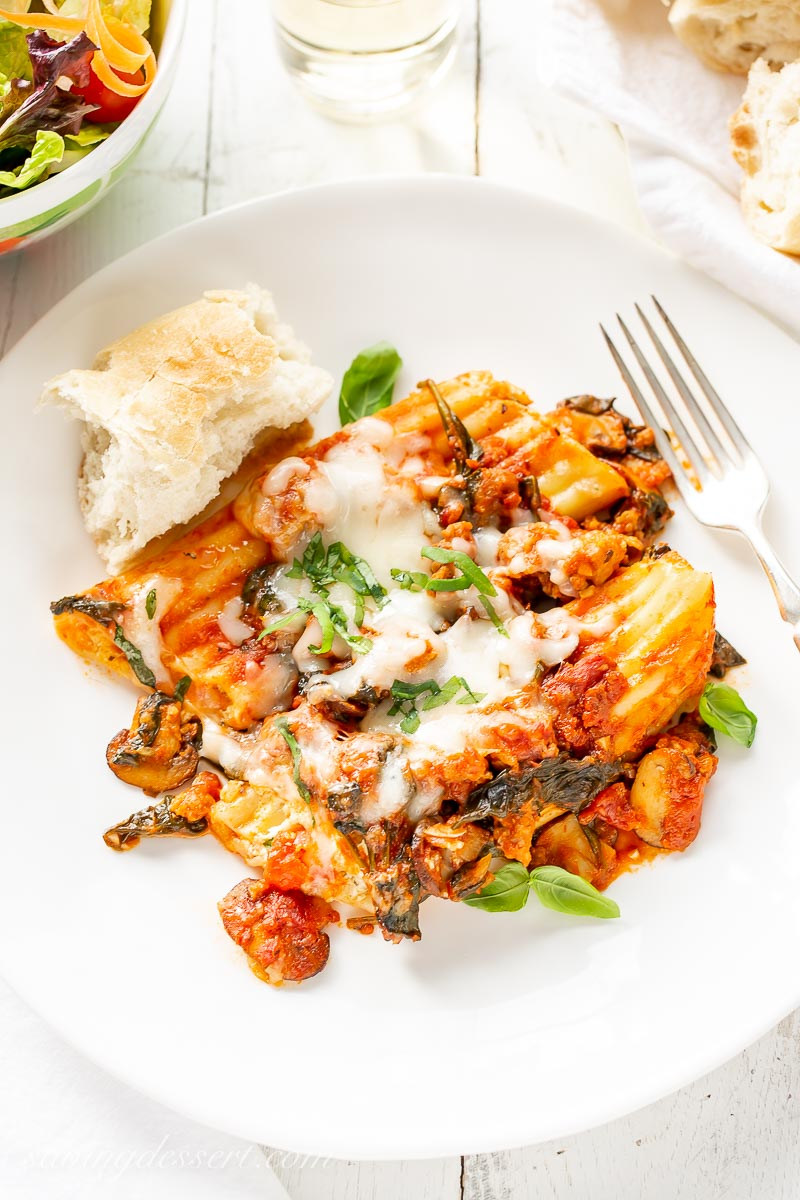 A plate with stuffed manicotti with mushrooms, sausage and spinach, and a piece of fresh baguette