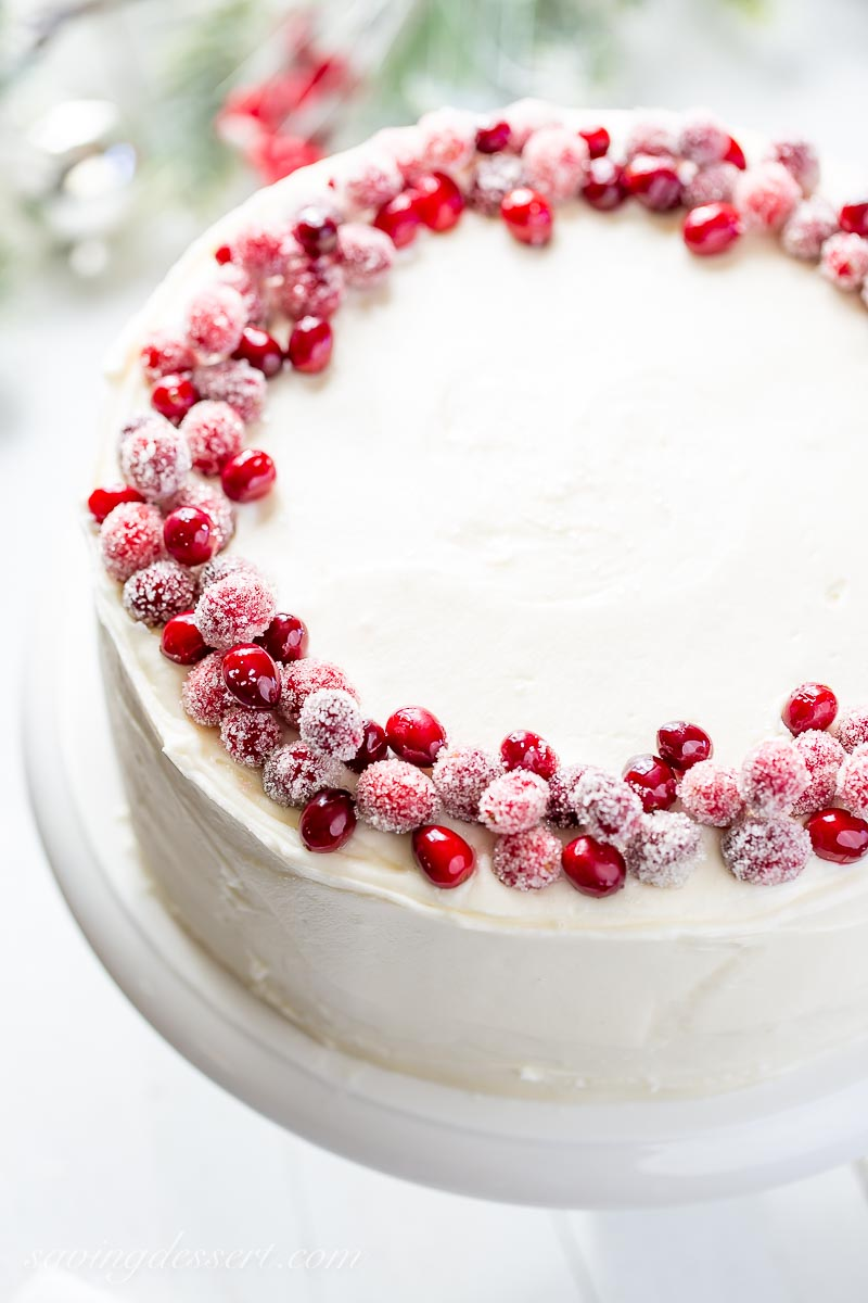 An overhead view of a white layer cake decorated with sugared cranberries