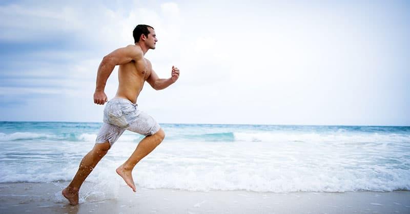 male athlete running on beach