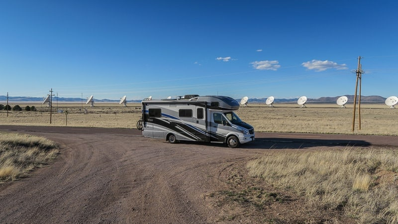 Winnebago View parked along the road with the satellites from the very large array in new mexico behind it