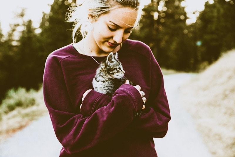 Image of a beautiful girl walking on a trail with her cat