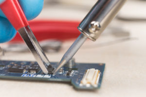 Hand with tweezers holding the chip, soldering iron solder it in place