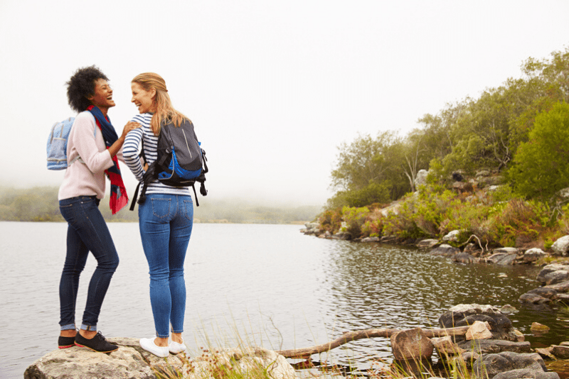 Two female friends hiking by a lake