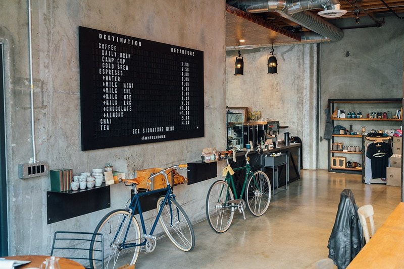 Two bikes lean on the wall inside a coffee shop