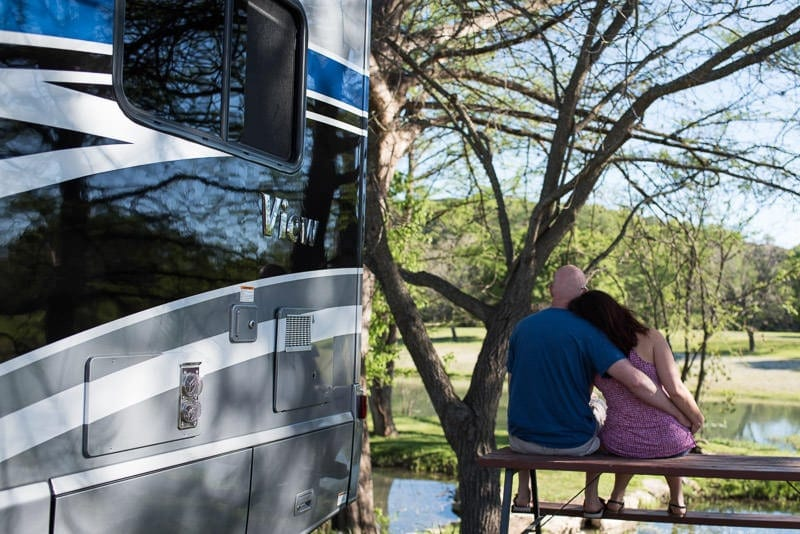 Brooke and Buddy sitting at a picnic table next to their RV overlooking a river
