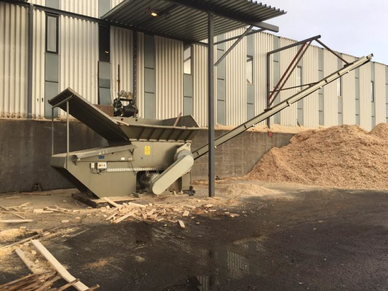 Wood Shredder With Wood Chips Under Conveyor-belt With Off Cut Wood On The Ground