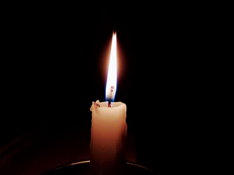 lit candle flame in darkness