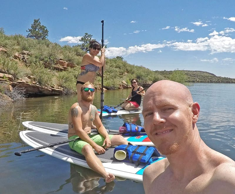 Brooke and Buddy paddleboarding with their friends on Horsetooth Resoivior in Fort Collins Colorado