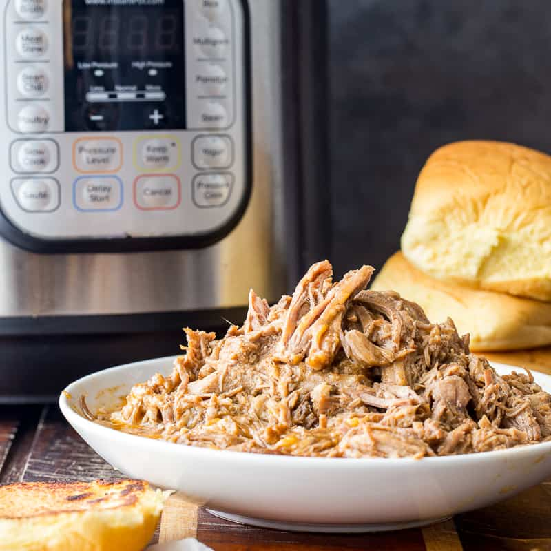 Instant Pot Pulled Pork in front of the Instant Pot with buns