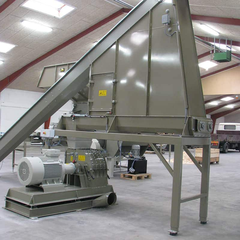 Buffer silo with angler conveyor feeding into hammer mill at Scanhuggers production hall