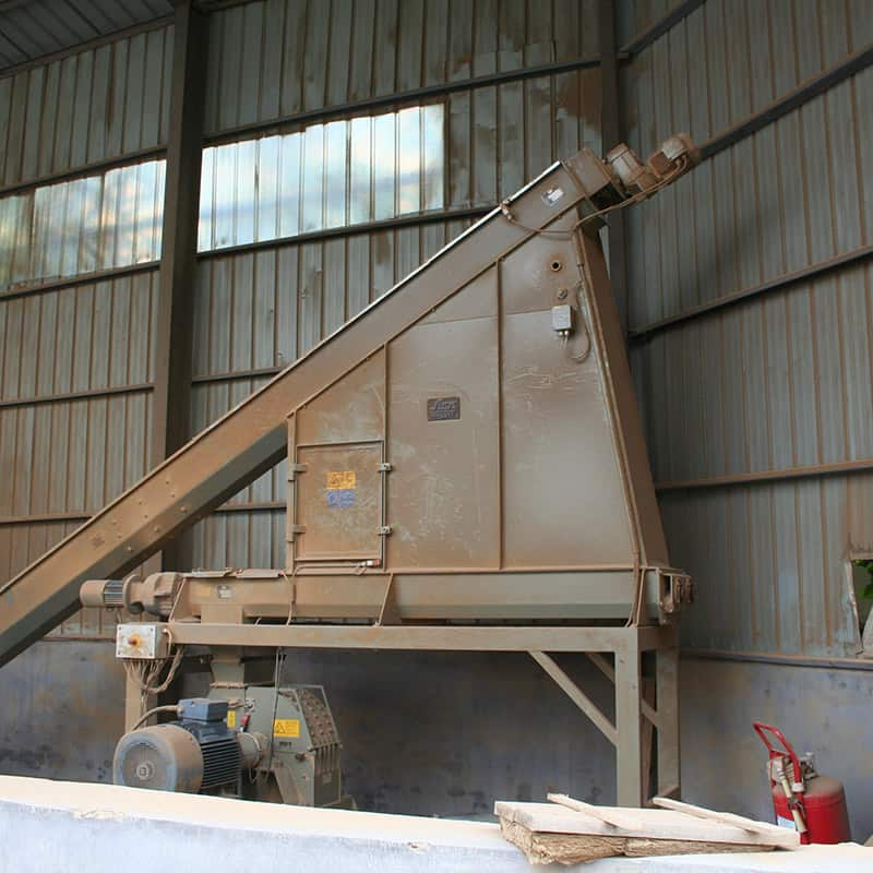 Buffer silo with angler conveyor feeding into hammer mill at a wood factory in China