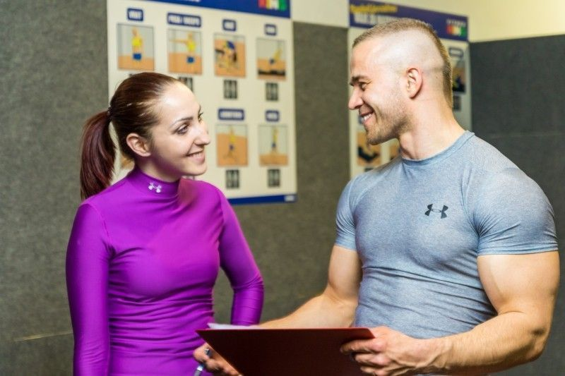 asesor-franquicia-gimnasios-young-woman-and-man-talking-in-fitness-club
