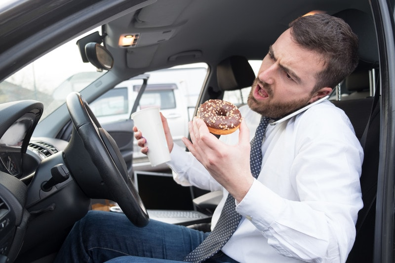 man eats a donut in the car