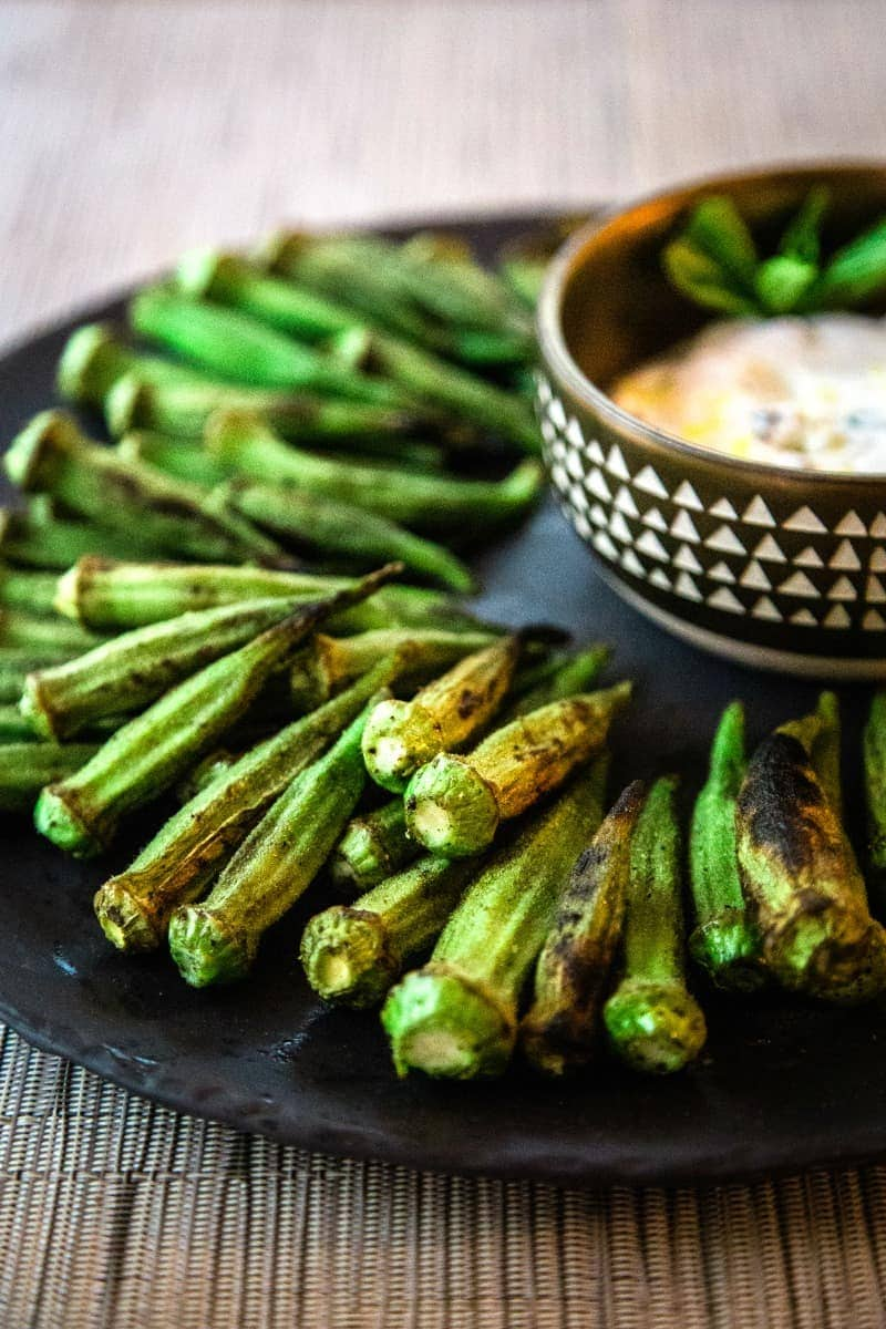 grilled whole okra pods on a black platter with dipping sauce
